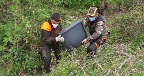 volontari che rimuovono un vecchio televisore dal bosco